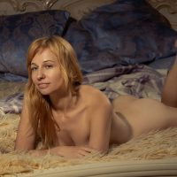 Beautiful nude woman in a boudoir photoshoot lying on her bed showing her beautiful body