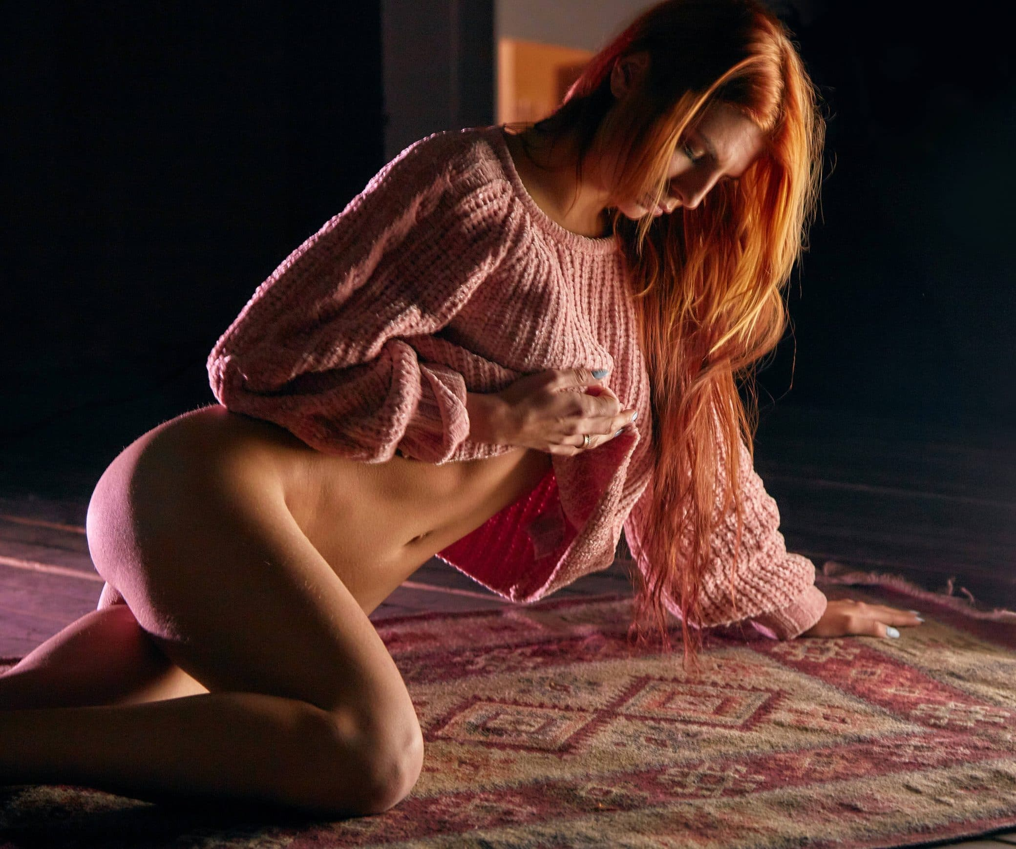 Beautiful sexy redhead woman modeling only wearing a knitted sweater lifting it to show her bum, sexy legs and stomach