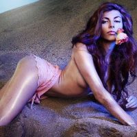 Beautiful woman lying in the sand with a rose in her mouth