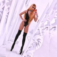 Beautiful blonde wearing a tight black bodysuit ans high heeled latex boots showing her magnificent body