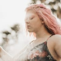 Beautiful pink haired woman wearing a black top in an artistic shoot