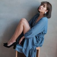 Beautiful asian woman sitting on a wooden cube wearing a blue dress and black heels holding her sexy legs up