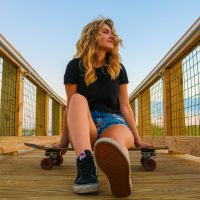 Beautiful blonde woman hanging with a skateboard wearing a black top and denim shorts looking at the horison with her long legs