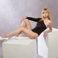 Beautiful blonde woman modeling wearing a black bodysuit ans white heels showing her fit body and long toned legs