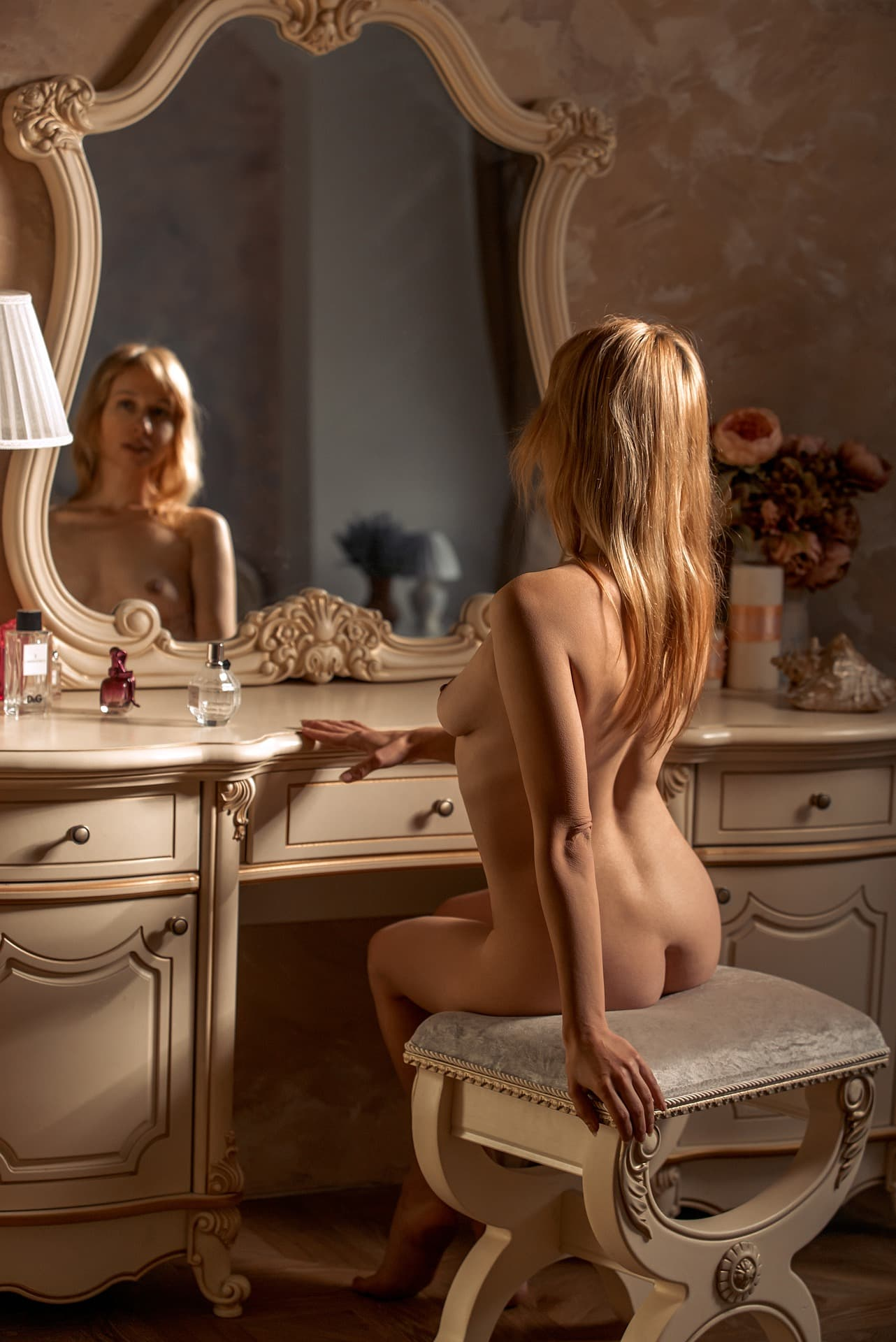 Beautiful blonde woman Victoria Borodinova sitting in the nude in front of a vintage dresser for a boudoir photoshoot
