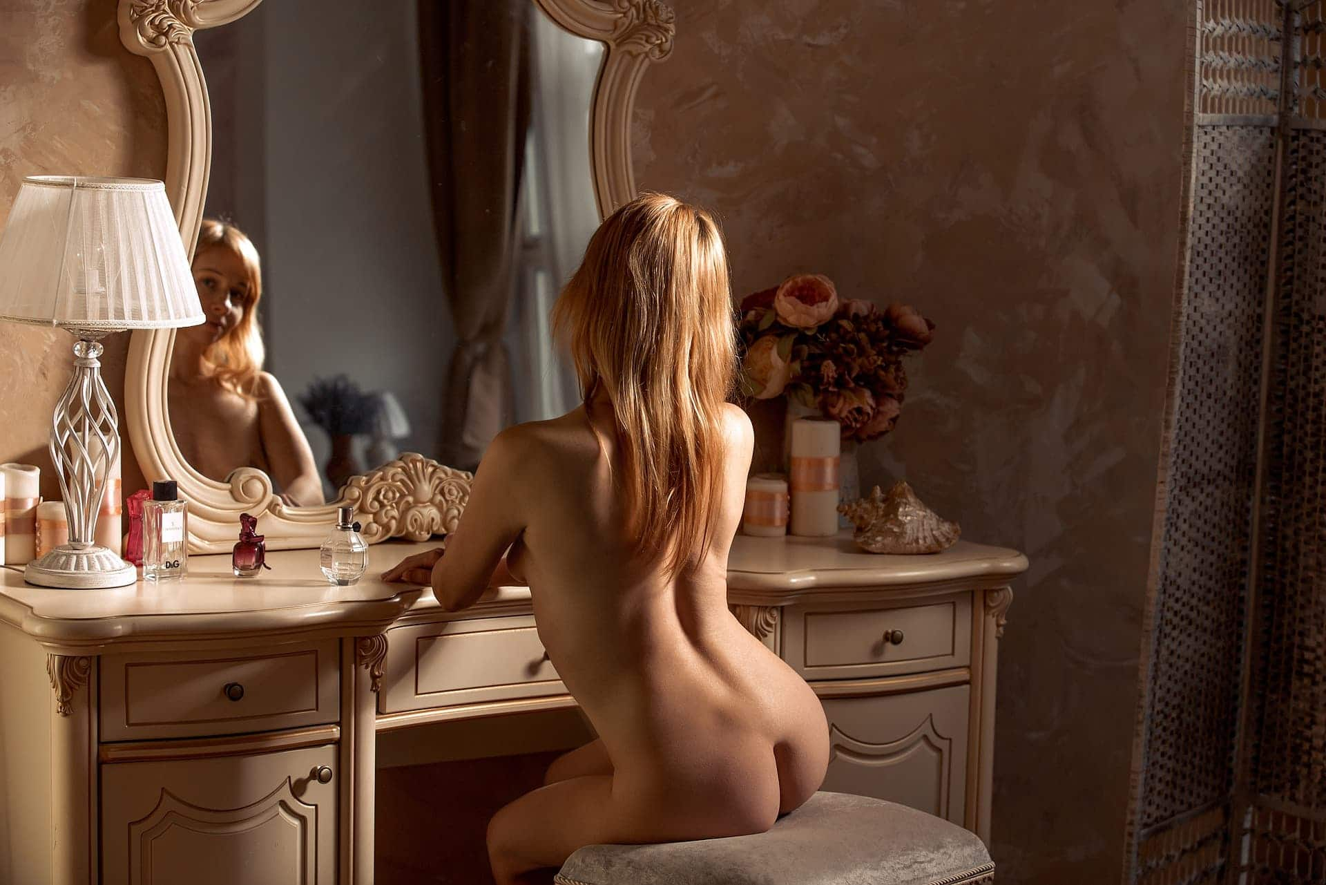 Beautiful blonde woman Victoria Borodinova sitting in the nude in front of a vintage dresser for a boudoir photoshoot showing her magnificent body