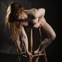 Beautiful woman posing in the nude on a wooden stool in a boudoir photoshoot bending with her legs wide open with hair in her face
