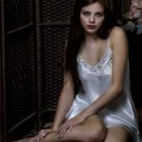 Beautiful woman sitting on the floor wearing a white satin night gown