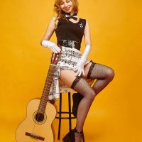 Beautiful retro pinup style woman wearing a white skirt and black fishnets stocking holding a guitar showing her sexy legs and inner thighs