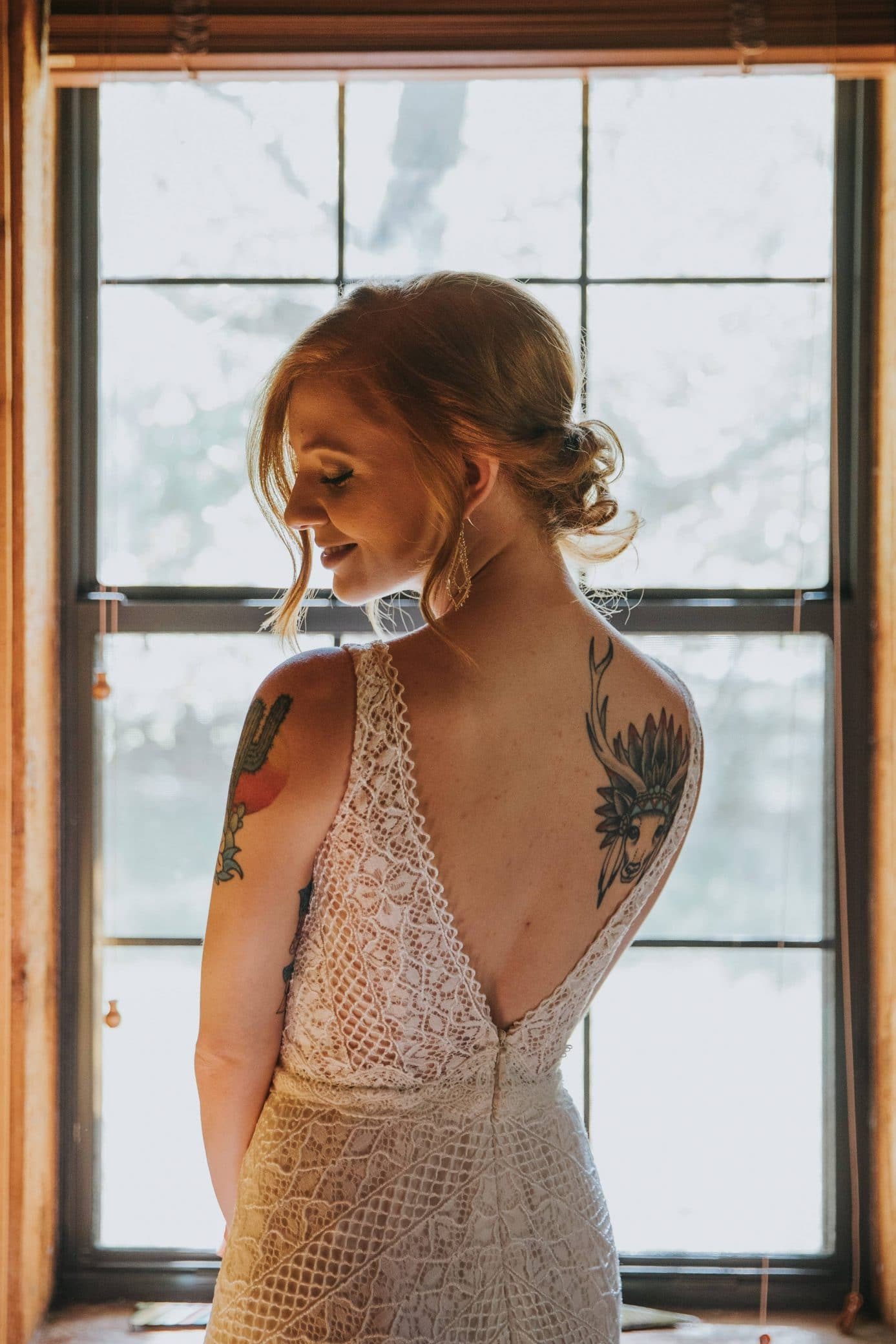 Beautiful redhead woman with tattoos wearing a bare back lace white dress looking over her shoulder
