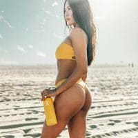 Beautiful woman in a beach photoshoot wearing a yellow bikini