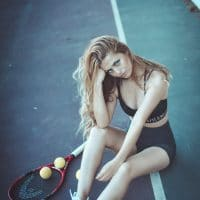 Beautiful blonde on a tennis court wearing black sportswear and white sneakers