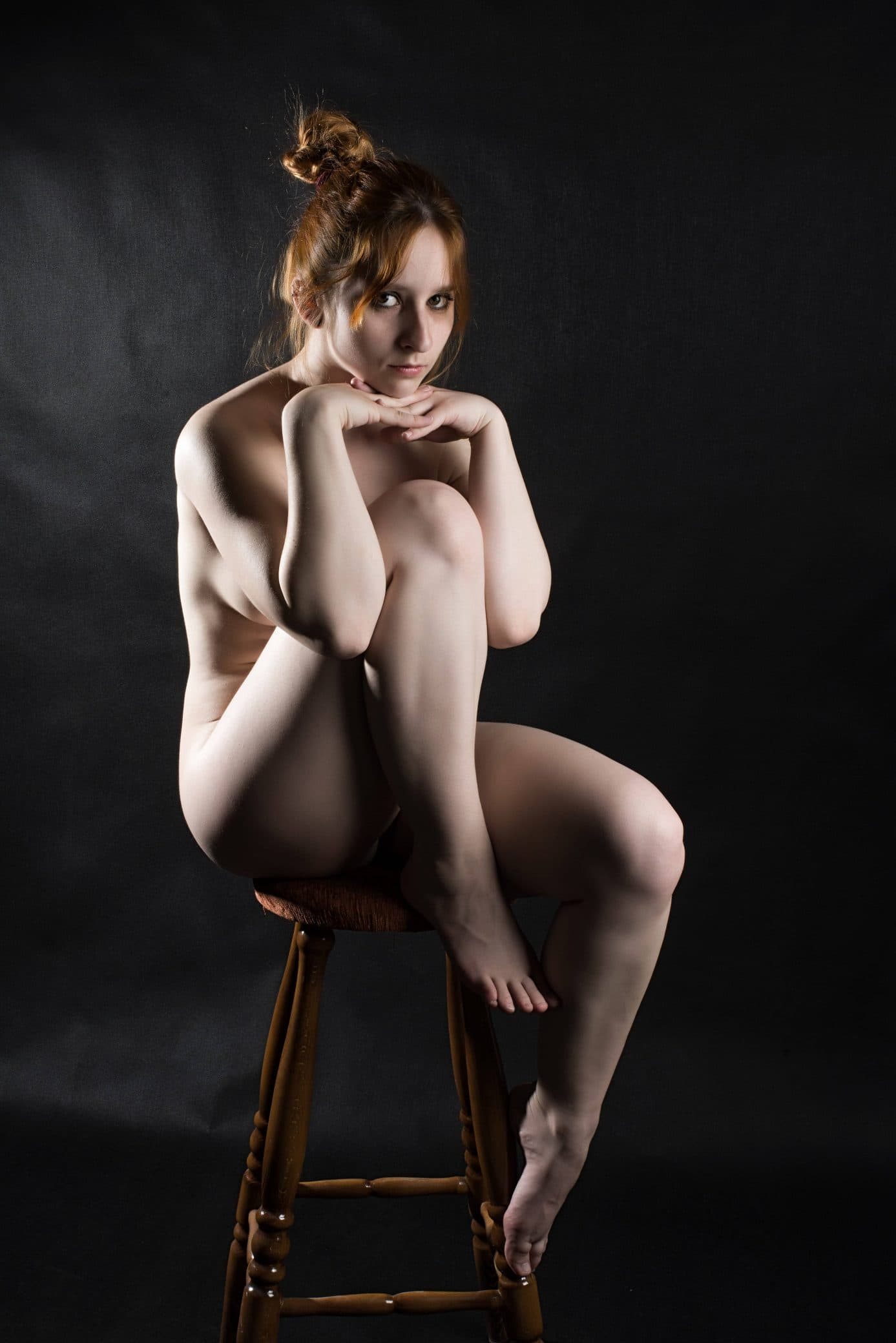 Beautiful redhead woman Fenyvesi Luca in a artistic boudoir photoshoot sitting on a wooden stool with her bare leg up showing her bare foot