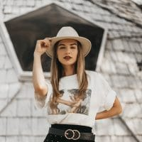 Beautiful woman modeling outside wearing a white t, short black skirt and black boots pinching the tip of her white hat