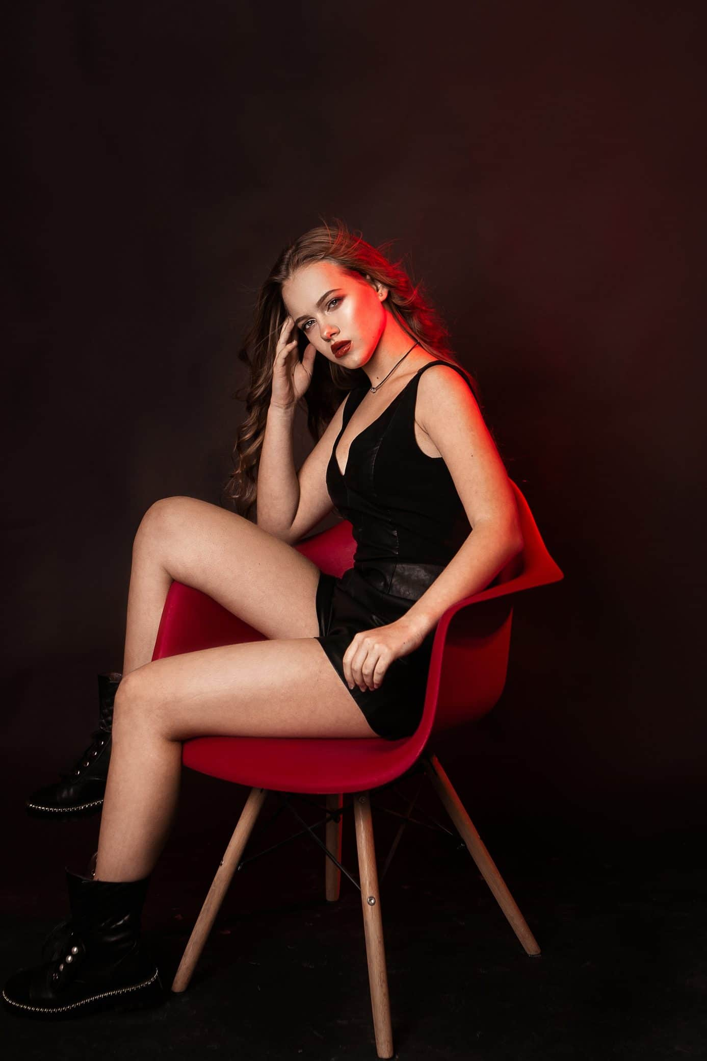 Beautiful women Ангелинка Angelina wearing a black dress and black boots sitting on a chair with one leg up holding her head for a photoshoot