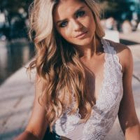 Beautiful portrait of a blonde smiling woman Kalyssa Alynn with blue eyes sitting on the side of the street wearing a white transparent lace top showing cleavage and denim jeans