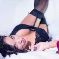 Beautiful green-eyed woman wearing black lingerie lying on her back in a close up shot