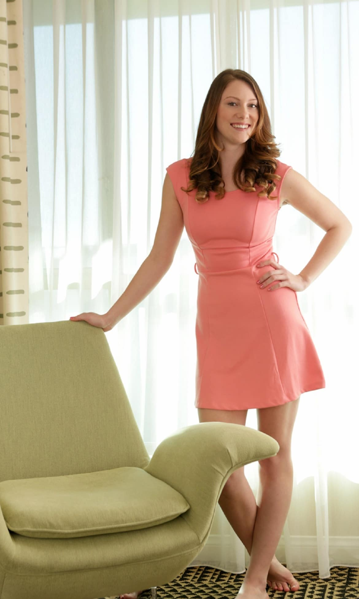 Beautiful brunette woman posing bare feet in a short pink dress smiling and standing up with her hand on her waist
