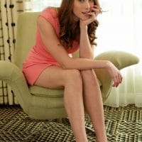 Beautiful brunette woman posing bare feet in a short pink dress sitting on a chair looking sexy with her finger in her mouth