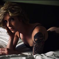 Beautiful blonde model wearing black lingerie for a boudoir photoshoot lying in a bed