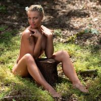 Beautiful Dutch blonde model Willeke Bartels sitting in the woods in the nude hiding her breast with her arms showing her sexy legs looking at the camera