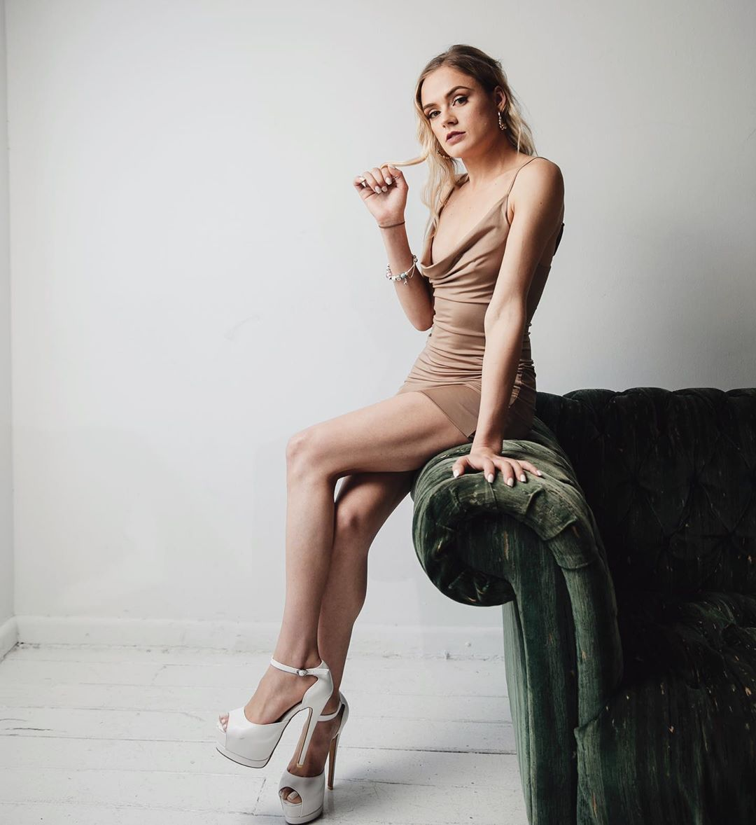 Beautiful blonde Australian model Bree Delamont wearing a tight dress and white high heels sitting on the arm of a green sofa with her sexy legs crossed playing with her hair