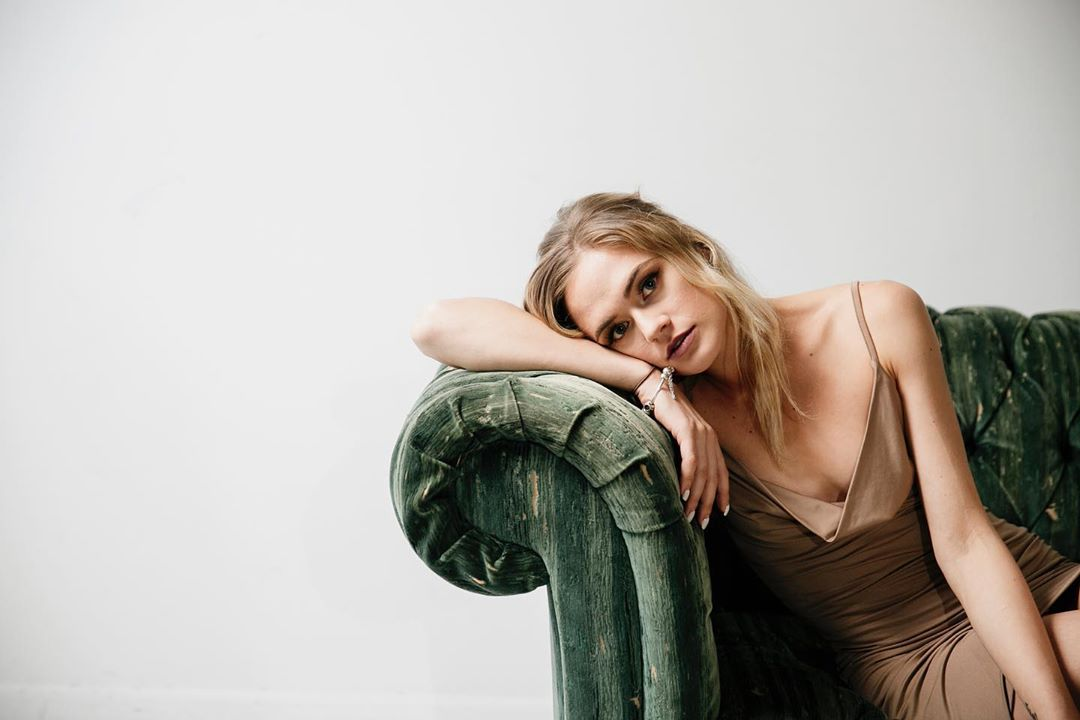 Beautiful blonde Australian model Bree Delamont resting her head on a green sofa looking back at the camera
