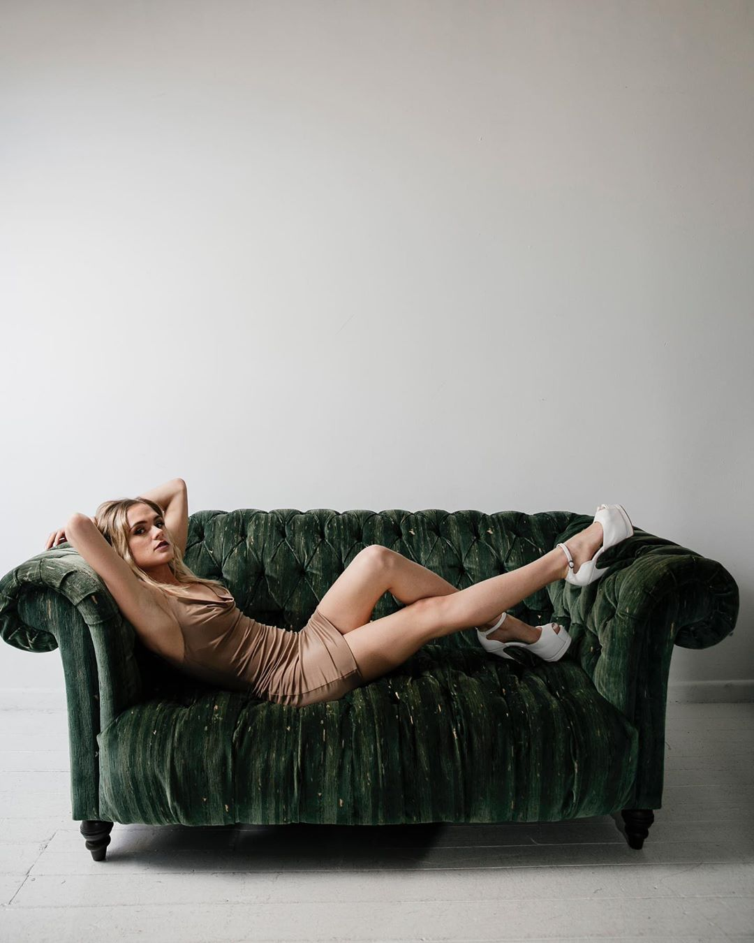 Beautiful blonde Australian model Bree Delamont wearing a tight dress and white high heels lying on a green sofa with her arms up behind her head showing her long bare legs