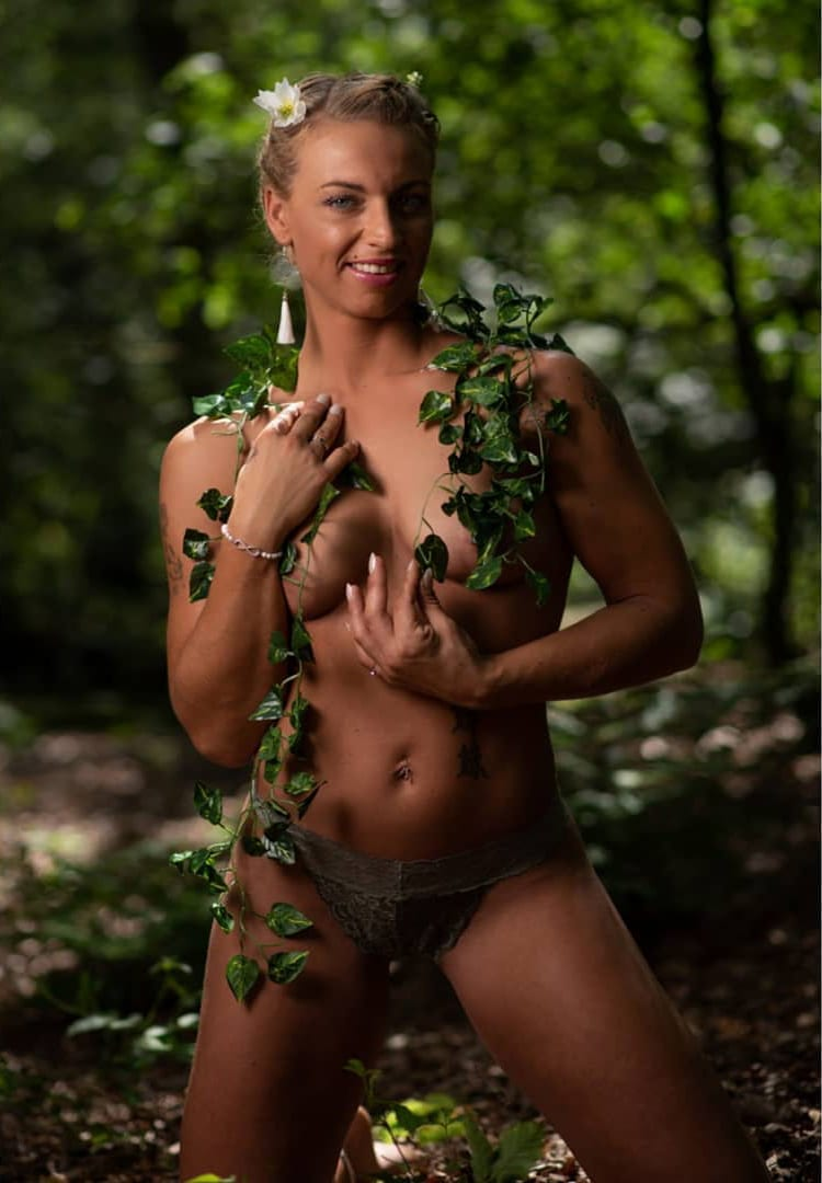 Beautiful Smiling Dutch blonde model Willeke Bartels in the woods for a bare photoshoot standing on her knees hiding with tree leaves and her hand showing her toned body
