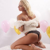 Beautiful smiling blonde woman in a party setup wearing black panties and a white fur coat