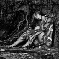 Beautiful woman Kate M sitting among roots wearing a white bikini in a black and white photoshoot looking at the camera