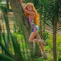 Beautiful model wearing a multicoloured dress and high heels for a photo session in nature