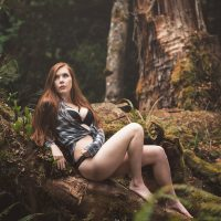 Beautiful Redhead woman Ally meowsparky from New Zealand wearing black lace lingerie barefoot sitting on a log showing her cleavage and sexy bare legs