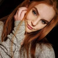 Beautiful blue eyed redhead woman Asia Skotarek portrait wearing a grey wool sweater