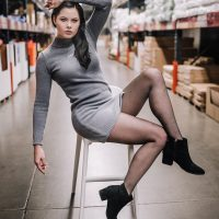 Beautiful woman Courtney Anderson wearing a gray wool short dress with black nylons and heeled boots doing a photoshoot in the middle of a store alley showing her sexy legs and inner thigh with her hand up