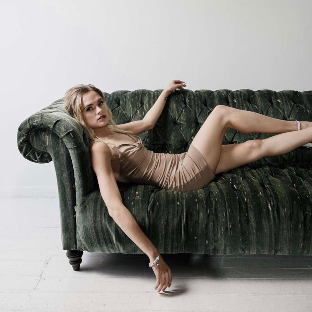 Beautiful blonde Australian model Bree Delamont wearing a tight dress and white high heels lying on a green sofa with her bare legs crossed looking at the camera