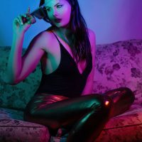 Beautiful model Courtney Anderson in a neon coloured photoshoot wearing a black top and tight pants sitting on a sofa removing her sunglasses showing cleavage