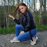 Beautiful redhead polish woman Asia Skotarek wearing a leather jacket, denim jeans and sneakers crouching and playing with her long hair