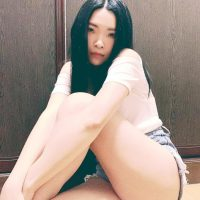 Beautiful woman sitting on the floor wearing ripped denim shorts and a white shirt