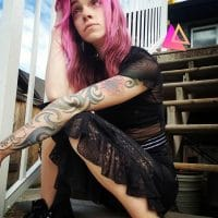 Beautiful Pink haired tattooed woman wearing goth clothes sitting in a yard