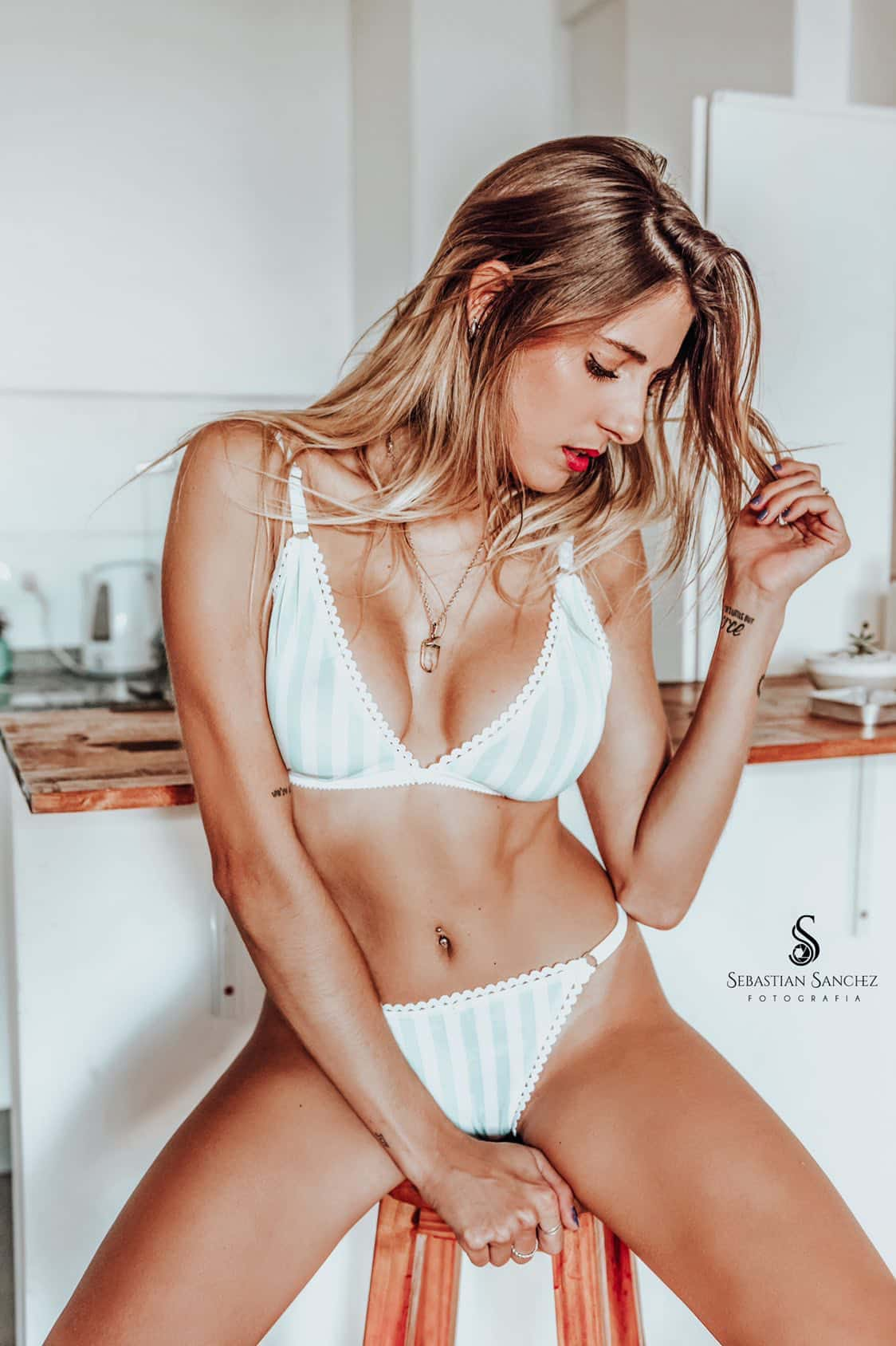 Beautiful Argentinian blonde model Camila Sol Botti sitting on a wooden stool only wearing striped white underwear showing cleavage looking down