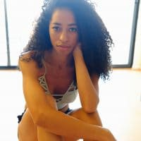 Beautiful portrait of a green eyed woman sitting on the floor looking back at the camera wearing short shorts and a white laced camisole showing cleavage and bare legs