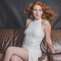 Beautiful redhead woman sitting in a classy white dress for a photo session