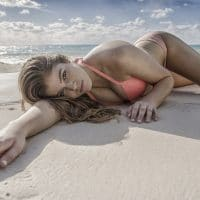 Beautiful blue eyed blonde woman wearing a peach bikini lying  in the sand on a beach