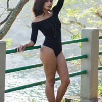 Beautiful woman wearing a black leotard and high heels for a photoshoot in the park