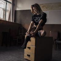 Beautiful woman wearing black knee socks and a t-shirt sitting on a wooden chest
