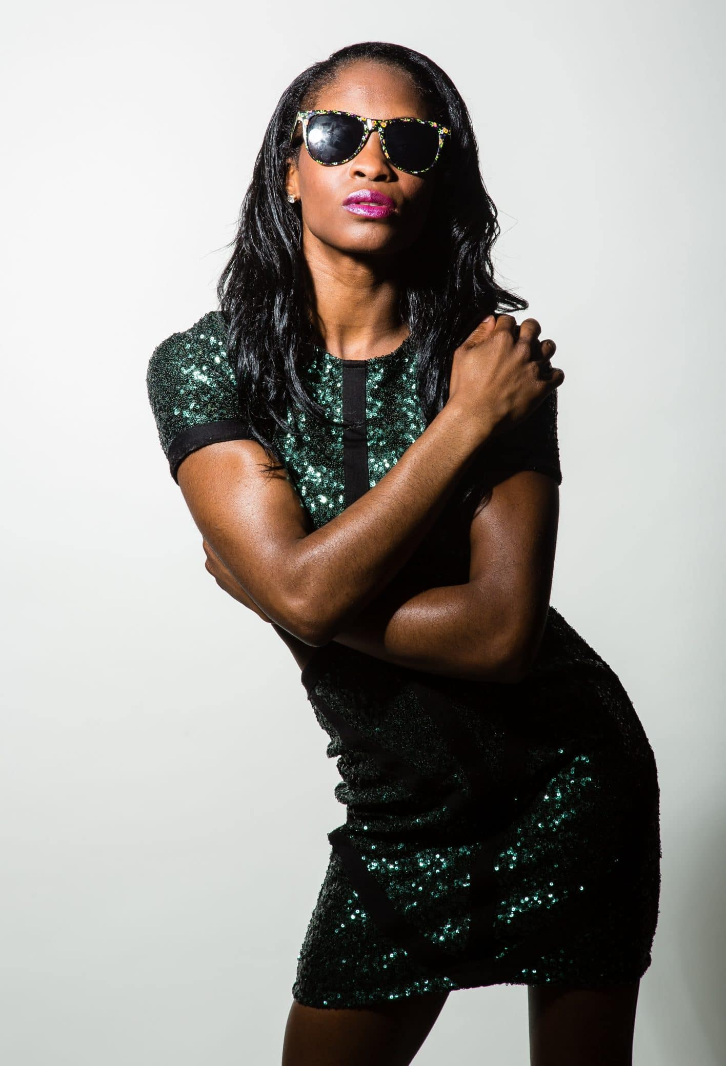 Beautiful black woman portrait wearing a tight sparkling green dress and sunglasses modelling for a studio photoshoot holding herself