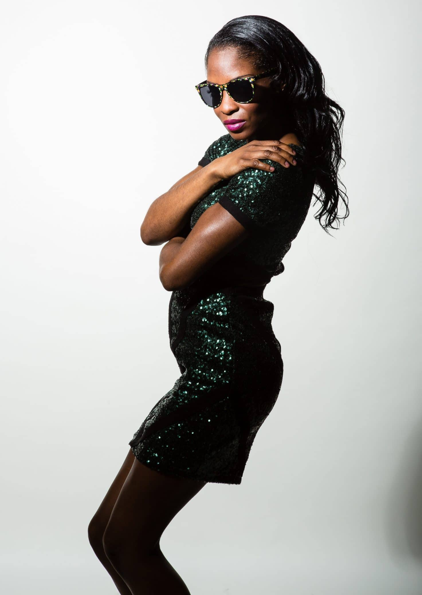Beautiful black woman wearing a tight sparkling green dress showing her right side with her arms to herself