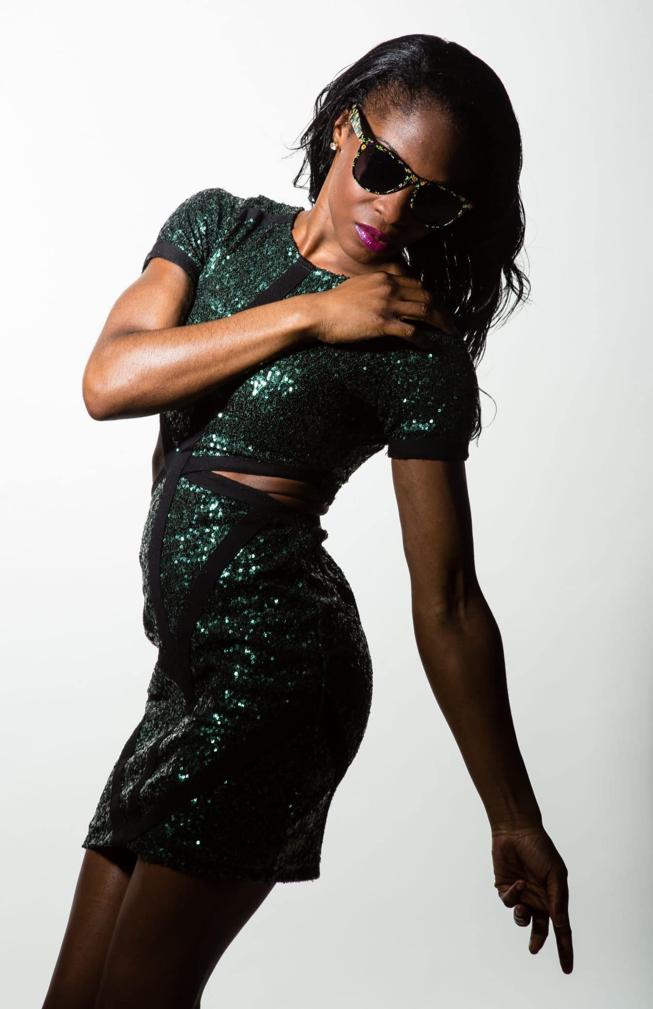 Beautiful black woman wearing a tight sparkling green dress modelling for a studio photoshoot with one arm down pointing to the floor