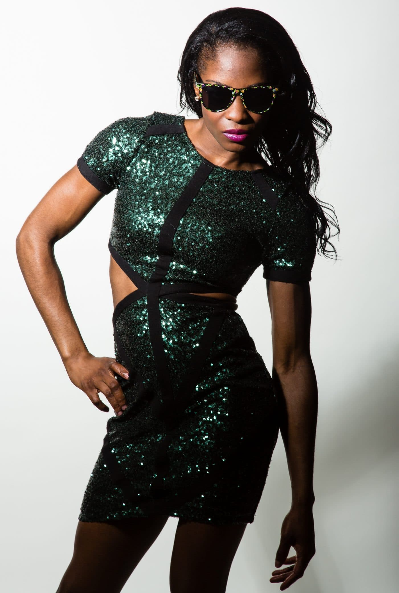 Beautiful black woman wearing a sparkling green dress opened on each side for a studio photoshoot with one hand on her waist